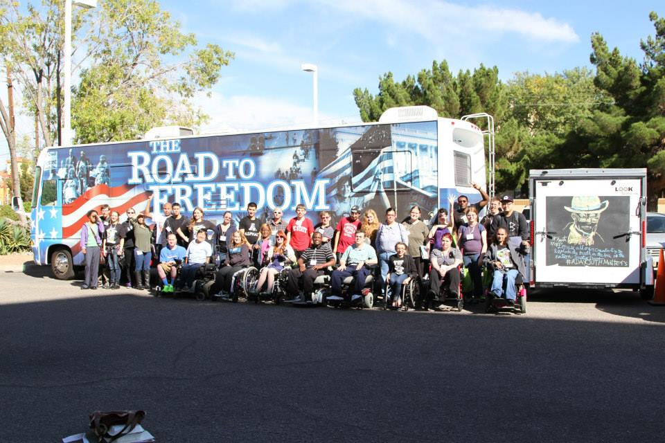 youth with disabilities standing in front of the road to freedom bus. to the right a chalk drawn picture of justin dart jr.