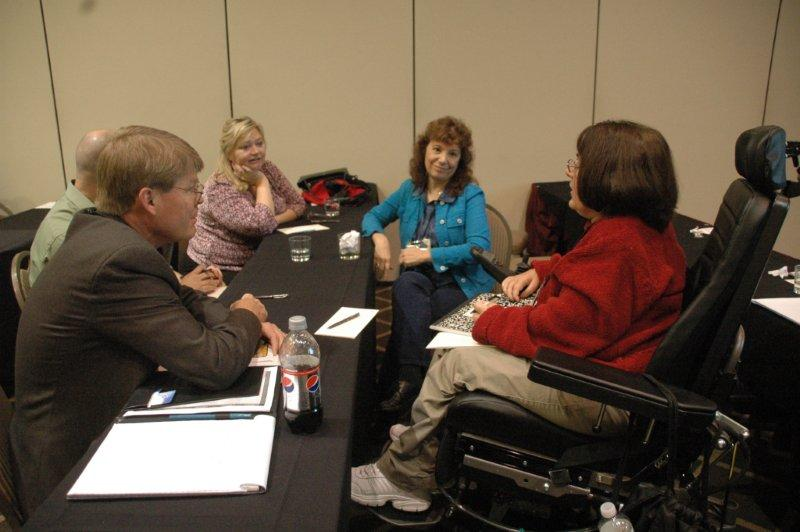 Pseron in mobility chair discussing workshop with 4 others