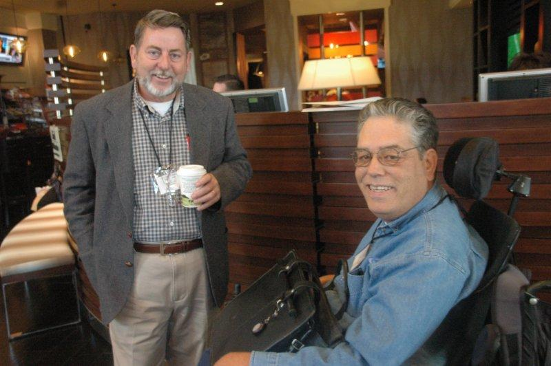 two men discussing conference with a cup of coffee