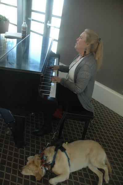 lady and guide dog playing a piano