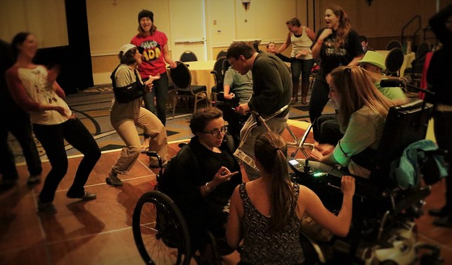 young women  in wheelchairs talking in the foreground, a young man using a walker dancing with a young lady with her arm in a cast. in the background women dancing and laughing